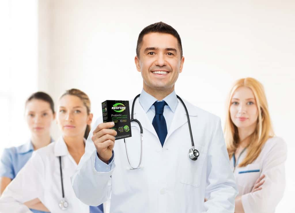 Daily Body Restore Probiotics Supplement - smiling male doctor in white coat with tablets over group of medics at hospital background